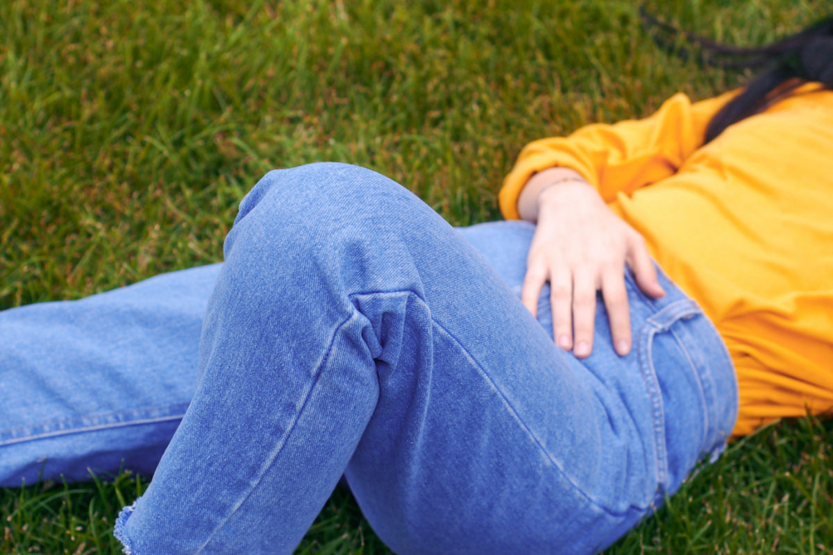 girl laying down on the grass holding her lower stomach