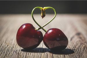 two cherries with their stems forming a heart shape