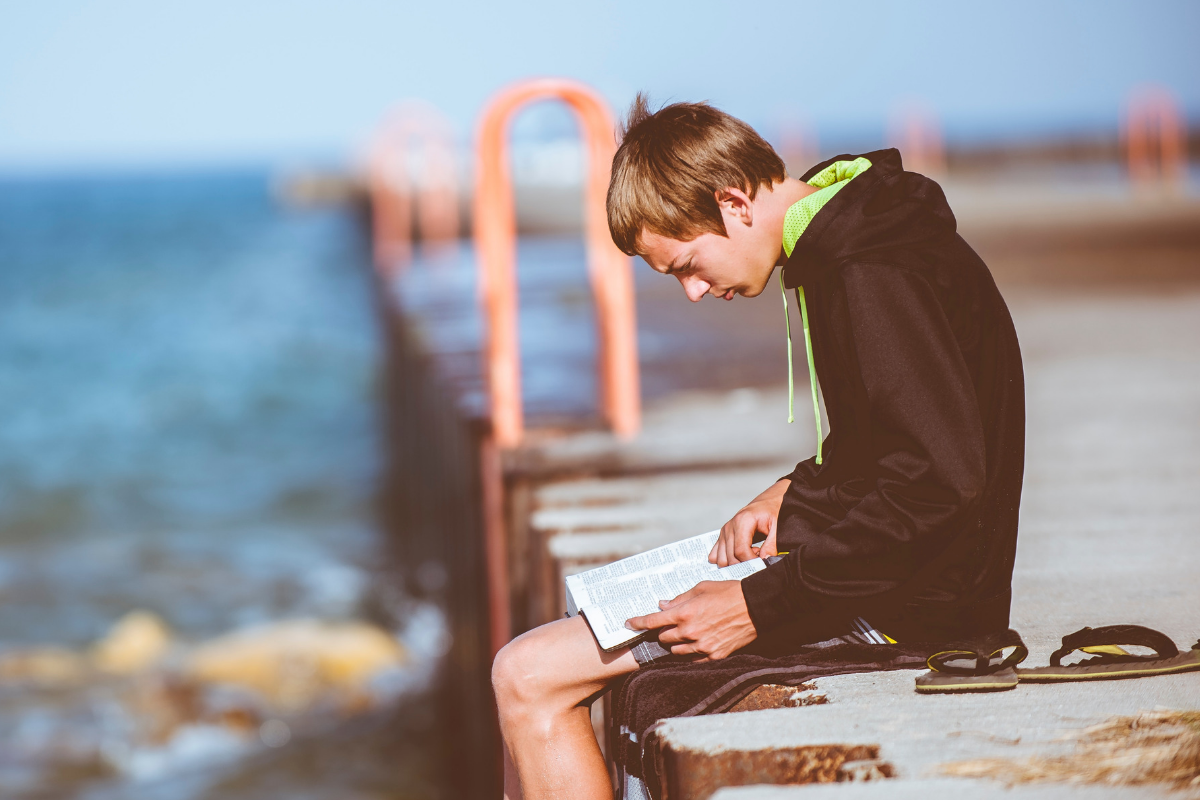teenage boy sat alone reading a book by the sea