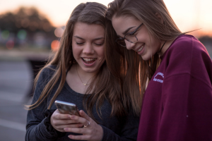 two girls looking at a phone and giggling