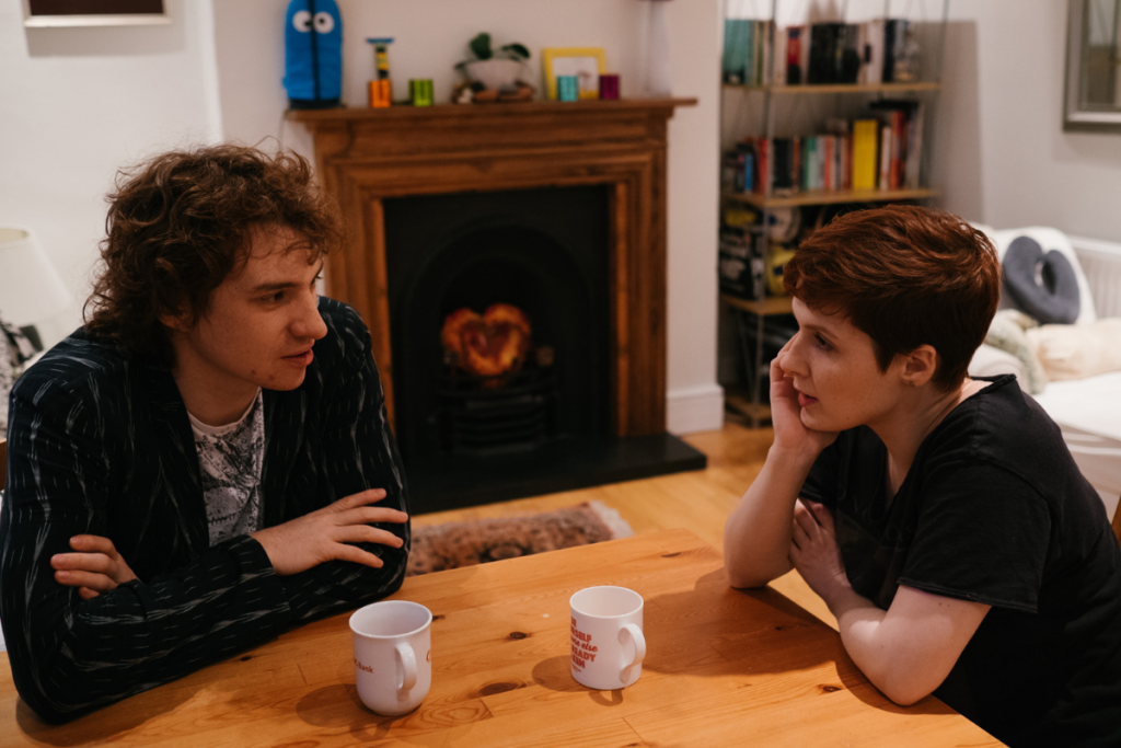 couple sat at kitchen table with cups of tea talking