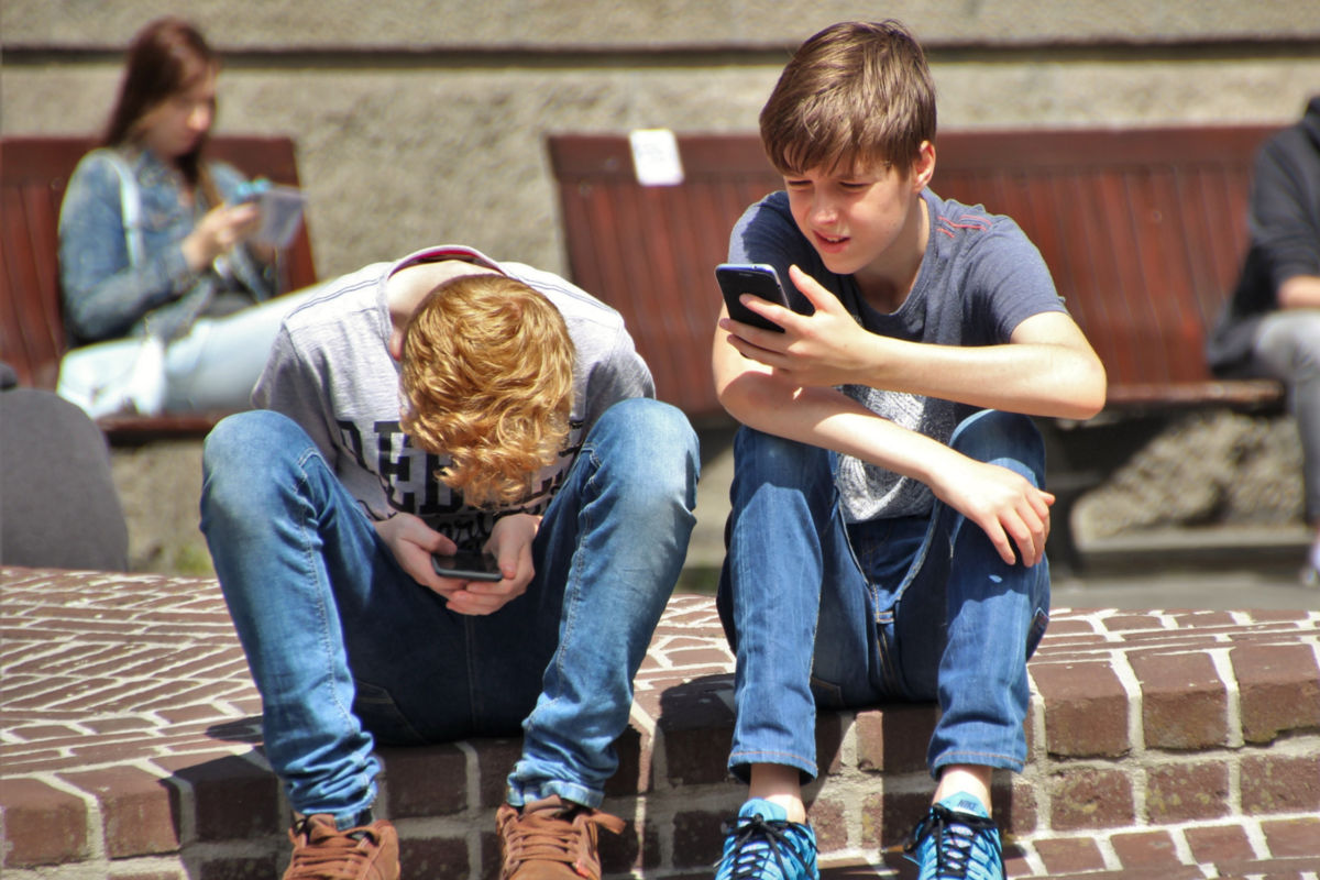 Two boys sitting on a step using their phones
