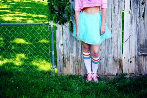 young person wearing a blue ballerina skirt with trainers on grass