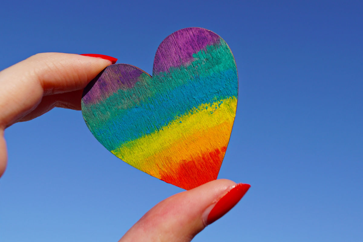 Rainbow heart being held up to the sky