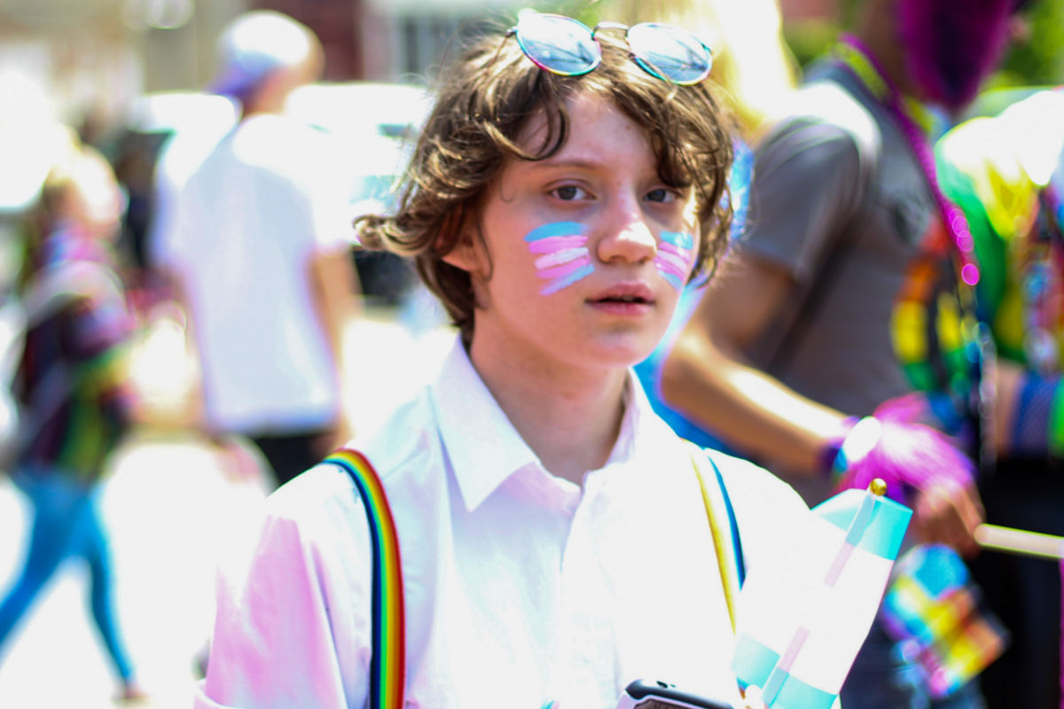 young person with a trans flag painted on their face