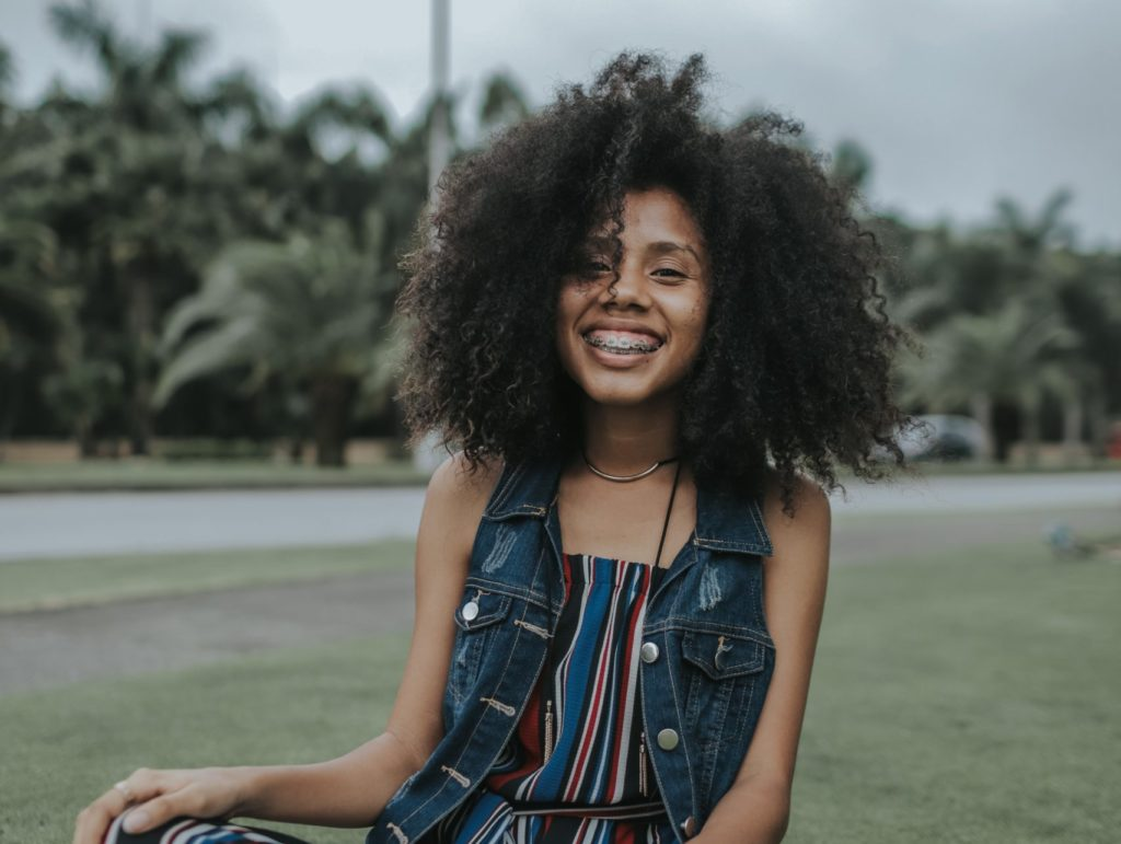 young person smiling widely in a park
