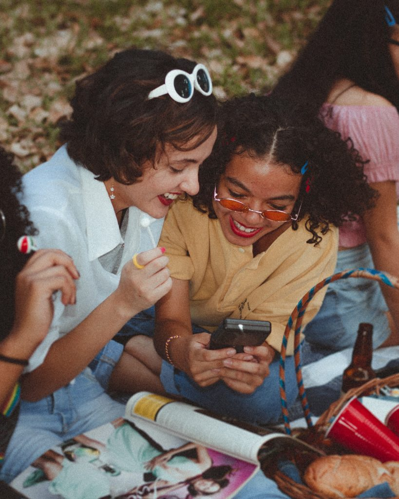 two young people smiling looking at a phone together