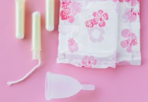 period products on a pink background: a menstrual cup, tampons and pads